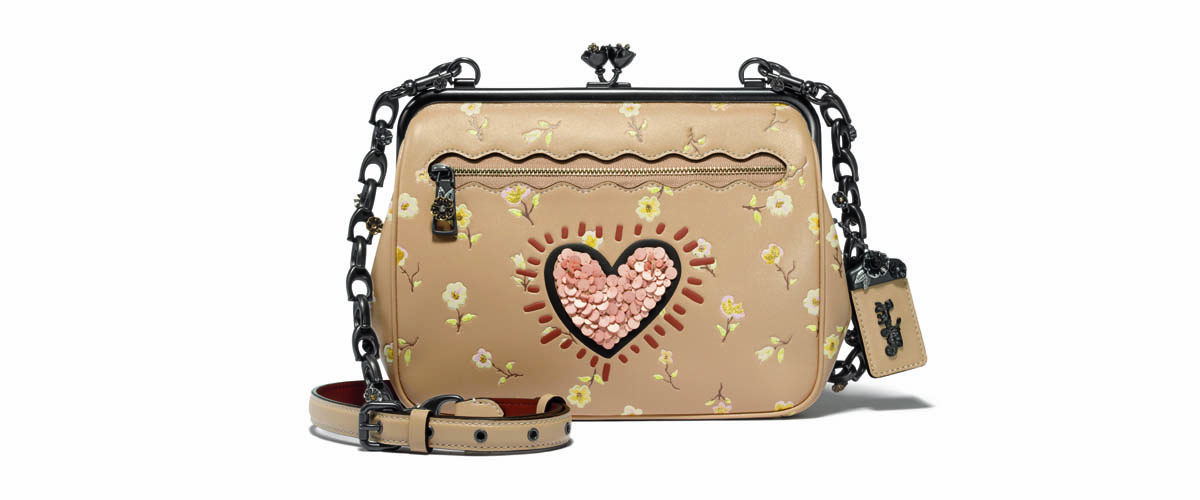The Kisslock Satchel With A Light Brown Base And Detailing With A Pink Heart And Black Straps Is A Fashionable New Handbag