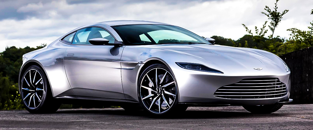 A light grey luxury car by aston martin on the road . It's sleek and elegant