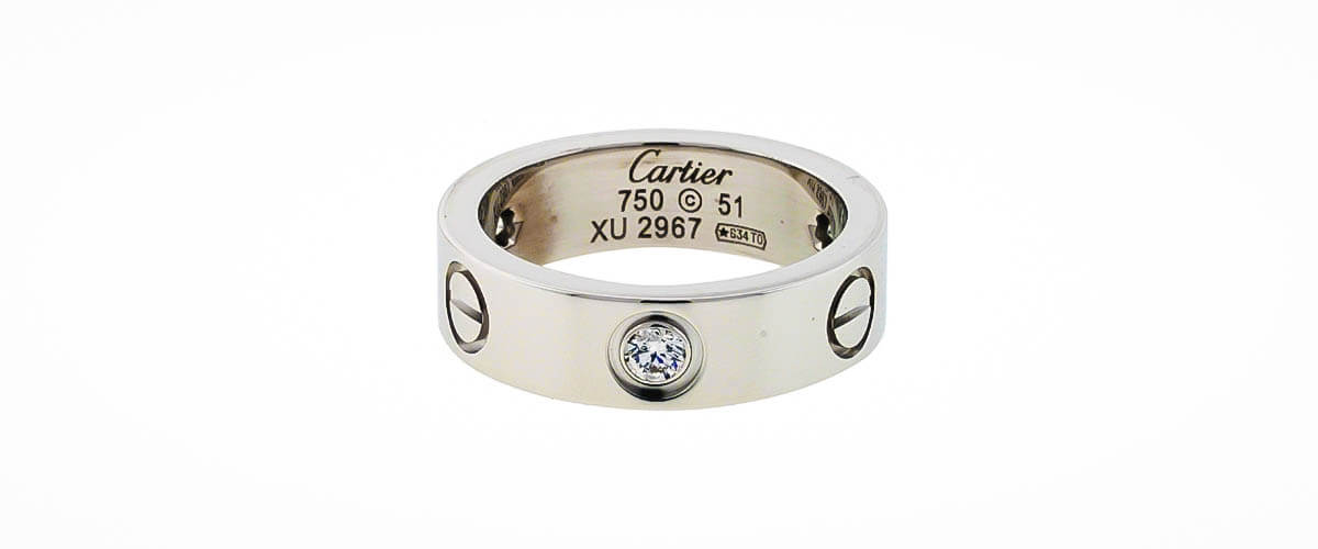 a carefully crafted silver colored stone studded ring carved wuth the name of the brand