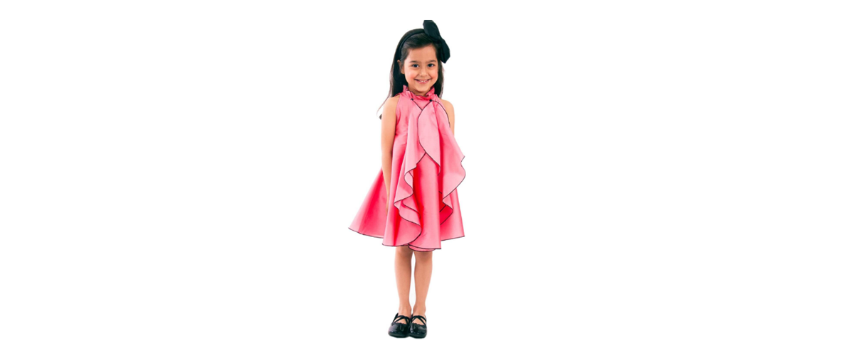 A kid model dressed in a designer pink frock and accessories to go with it.