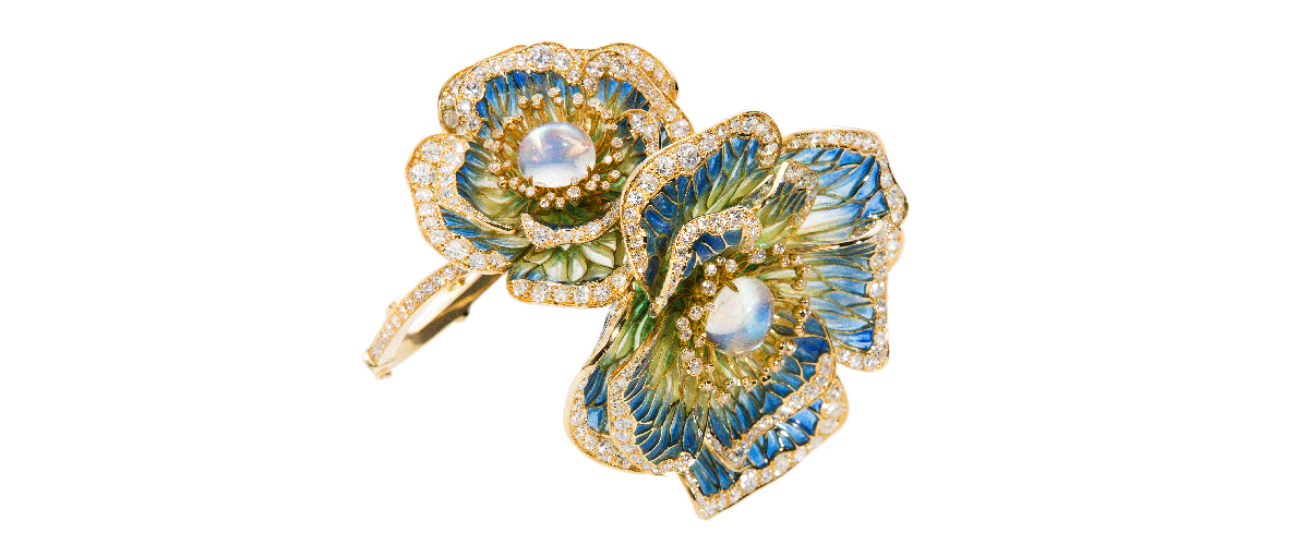 A delicately designed flower jewellery piece with details in a combination of fresh blue and green, embellished with diamonds.