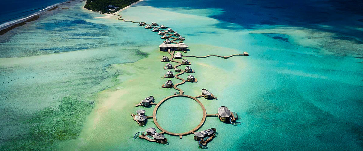 An aerial view of luxury resort Soneva Jani, Maldives, Villas surrounded by blue-green sea water and endless blue sky private island