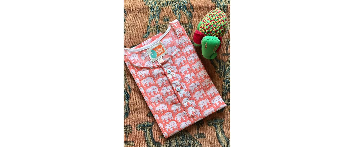 A printed white and pink tee shirt for babies, designed to look pretty on a petite body.