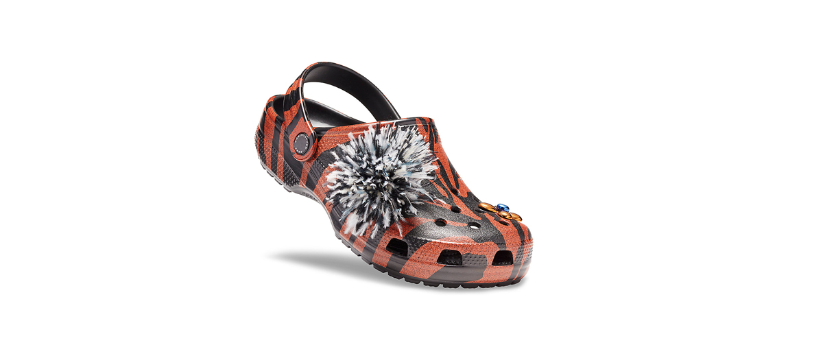 Creatively printed footwear luxury offered by crocs, adorned with a fashionable shoe accessory adding style quotient to comfort.