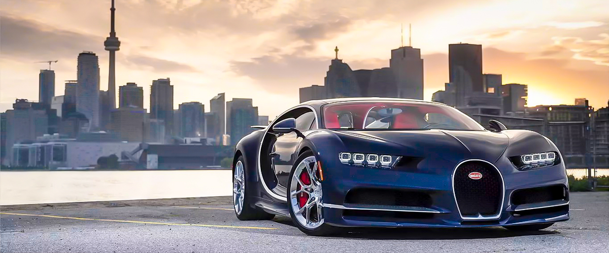A shiny new Bugatti Chiron with such a cool and unique sports car design and red seats.