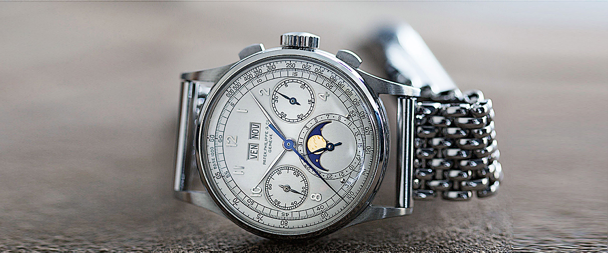 A Silver Watch By Patek Phillipe Swiss Luxury Wristwatch With White Dial And Blue Detailing